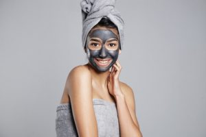 pretty smiling woman with a towel on head and facial mask on